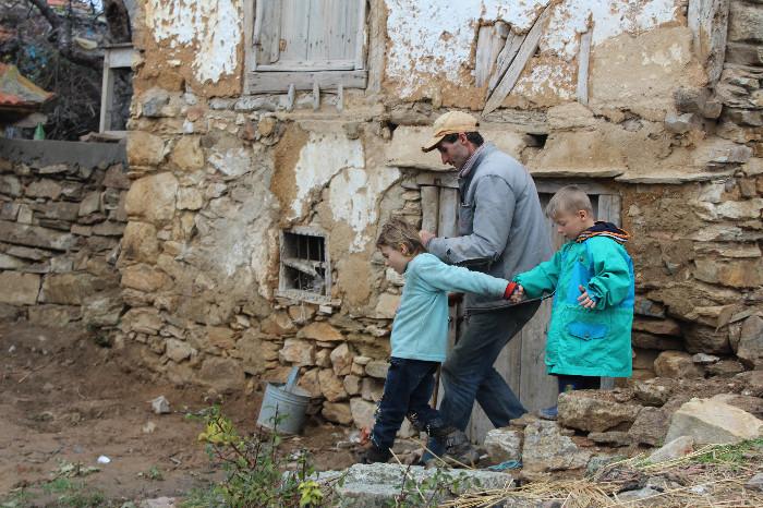 Стрмниот двор и распаднатите помошни објекти дополнително го отежнуваат движењето на Новко, па по потреба го водат двете најмали дечиња, цврсто фатени за рака едни за други (Фото: СДК.МК)